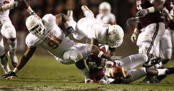 COLLEGE STATION, TX - NOVEMBER 26: Quarterback Jerrod Johnson #1 of the Texas A&M Aggies loses control of the ball as defensive tackle Kheeston Randall #91 and linebacker Roddrick Muckelroy #38 of the Texas Longhorns go for the loose ball in the first hal