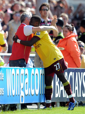 BLACKPOOL, ENGLAND - APRIL 10: Emmanuel Eboue of Arsenal celebrates scoring his side's second goal with a supporter during the Barclays Premier League match between Blackpool and Arsenal at Bloomfield Road on April 10, 2011 in Blackpool, England.  (Photo