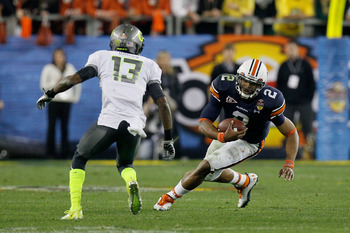 GLENDALE, AZ - JANUARY 10:  Cameron Newton #2 of the Auburn Tigers runs down field against Cliff Harris #13 of the Oregon Ducks during the Tostitos BCS National Championship Game at University of Phoenix Stadium on January 10, 2011 in Glendale, Arizona.