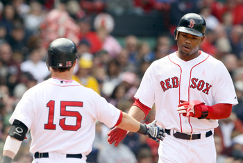 BOSTON, MA - MAY 08:  Carl Crawford #13 of the Boston Red Sox is congratulated by Dustin Pedroia #15 after Crawford scored in the third inning against the Minnesota Twins on May 8, 2011 at Fenway Park in Boston, Massachusetts.  (Photo by Elsa/Getty Images