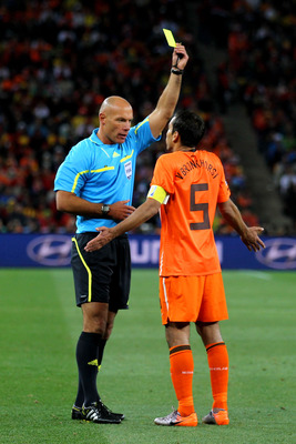 JOHANNESBURG, SOUTH AFRICA - JULY 11:  Referee Howard Webb issues Giovanni Van Bronckhorst of the Netherlands a yellow card during the 2010 FIFA World Cup South Africa Final match between Netherlands and Spain at Soccer City Stadium on July 11, 2010 in Jo