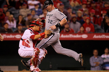 ANAHEIM, CA - MAY 11:  Adam Dunn #32 of the Chicago White Sox scores an insurance run in the tenth inning on a sacrifice fly ahead of the tag by catcher Hank Conger #16 of the Los Angeles Angels of Anaheim on May 11, 2011 at Angel Stadium in Anaheim, Cali