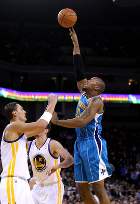 OAKLAND, CA - JANUARY 26:  David West #30 of the New Orleans Hornets shoots over Andris Biedrins #15 of the Golden State Warriors at Oracle Arena on January 26, 2011 in Oakland, California.  NOTE TO USER: User expressly acknowledges and agrees that, by do