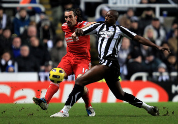 NEWCASTLE, UNITED KINGDOM - DECEMBER 11:  Sotirios Kyrgiakos of Liverpool challenges Shola Ameobi of Newcastle United during the Barclays Premier League match between Newcastle United and Liverpool at St James' Park on December 11, 2010 in Newcastle, Engl