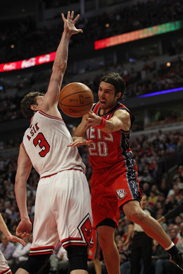 CHICAGO, IL - APRIL 13: Sasha Vujacic #20 of the New Jersey Nets passes the ball around Omer Asik #3 of the Chicago Bulls at United Center on April 13, 2011 in Chicago, Illinois. NOTE TO USER: User expressly acknowledges and agrees that, by downloading an