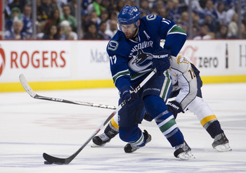 VANCOUVER, CANADA - MAY 7: Ryan Kesler #17 of the Vancouver Canucks skates with the puck while being pursued by Mike Fisher #12 of the Nashville Predators during the third period in Game Five of the Western Conference Semifinals during the 2011 NHL Stanle