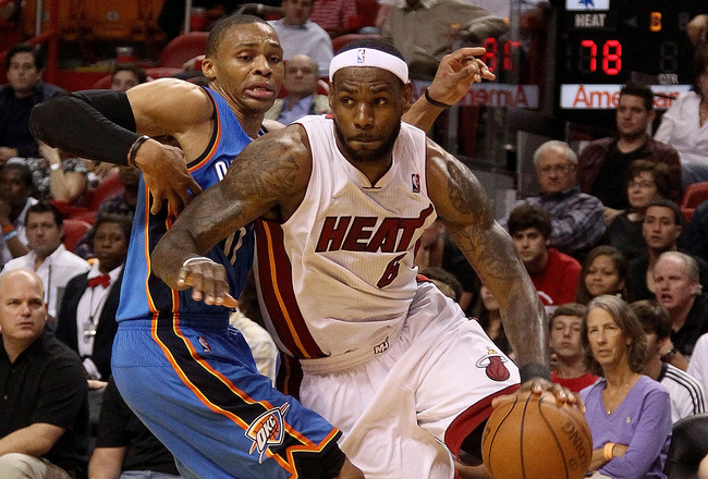 MIAMI, FL - MARCH 16:  LeBron James #6 of the Miami Heat drives by Russell Westbrook #0 of the Oklahoma City Thunder during a game at American Airlines Arena on March 16, 2011 in Miami, Florida. NOTE TO USER: User expressly acknowledges and agrees that, b