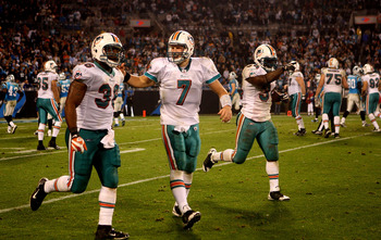 CHARLOTTE, NC - NOVEMBER 19:  Chad Henne #7 and teammates Lousaka Polite #36 and Ricky Williams #34 of the Miami Dolphins celebrate as they run off the field after a touchdown against the Carolina Panthers during their game at Bank of America Stadium on N