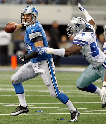 ARLINGTON, TX - NOVEMBER 21:  Quarterback Shaun Hill #14 of the Detroit Lions scrambles with the ball under pressure by Demarcus Ware #94 of the Dallas Cowboys at Cowboys Stadium on November 21, 2010 in Arlington, Texas.  The Cowboys beat the Lions 35-19.