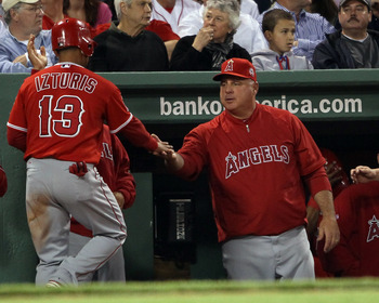 BOSTON, MA - MAY 02:  Maicer Izturis #13 of the Los Angeles Angels is congratulated by manager Mike Scioscia #14 after Izturis scored in the third inning against the Boston Red Sox on May 2, 2011 at Fenway Park in Boston, Massachusetts.  (Photo by Elsa/Ge