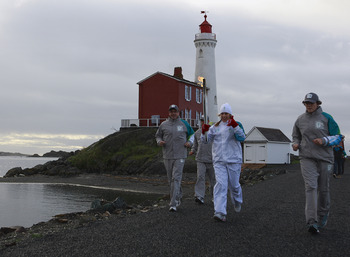 COLWOOD, BRITISH COLUMBIA - OCTOBER 31:   Laura Mongeau carries the Olympic torch during the Olympic Torch relay on October 31, 2009 in front of Fisgard Lighthouse at Fort Rodd Hill National Historic Site in Colwood, British Columbia, Canada.  The Olympic