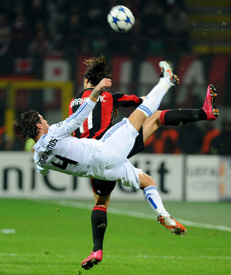 MILAN, ITALY - NOVEMBER 03: Zlatan Ibrahimovic of AC Milan goes up for the ball against Sergio Ramos of Real Madrid during the Uefa Champions League group G match between AC Milan and Real Madrid at Stadio Giuseppe Meazza on November 3, 2010 in Milan, Ita