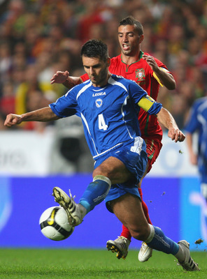 LISBON, PORTUGAL - NOVEMBER 14:  Simao Sabrosa of Portugal tangles with Emir Spahic of Bosnia during the FIFA 2010 European World Cup qualifier first leg match between Portugal and Bosnia-Herzegovina at the Luz stadium on November 14, 2009 in Lisbon, Port
