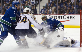 VANCOUVER, CANADA - APRIL 30: Goalie Roberto Luongo #1 of the Vancouver Canucks stops Matt Halischuck #24 of the Nashville Predators in close during the first period in Game Two of the Western Conference Semifinals during the 2011 NHL Stanley Cup Playoffs