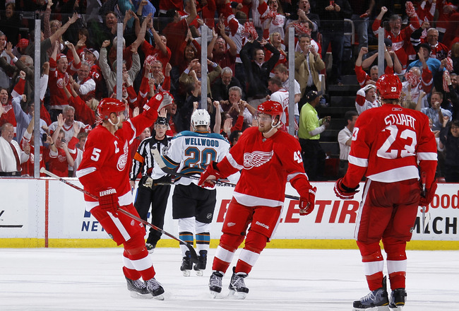 DETROIT - MAY 10: Darren Helm #43 of the Detroit Red Wings celebrates his third period empty net goal with Nicklas Lidstrom #5 and Brad Stuart #23 while playing the San Jose Sharks in Game Six of the Western Conference Semifinals during the 2011 NHL Stanl