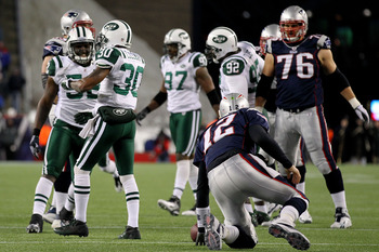 FOXBORO, MA - JANUARY 16:  Tom Brady #12 of the New England Patriots gets up after being sacked by Drew Coleman #30 of the New York Jets during their 2011 AFC divisional playoff game at Gillette Stadium on January 16, 2011 in Foxboro, Massachusetts.  (Pho