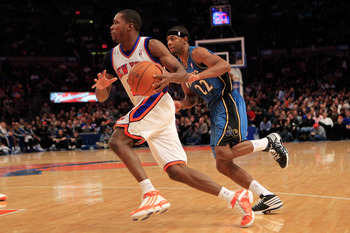 NEW YORK, NY - JANUARY 24: Toney Douglas #23 of the New York Knicks drives past Mustafa Shakur #22 of the Washington Wizards at Madison Square Garden on January 24, 2011 in New York City. NOTE TO USER: User expressly acknowledges and agrees that, by downl