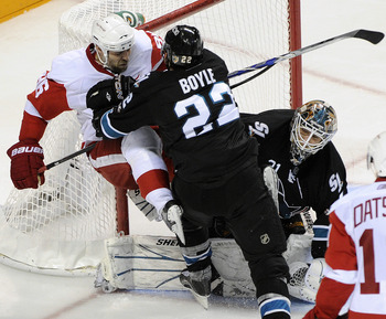 SAN JOSE, CA - MAY 12: Dan Boyle #22 of the San Jose Sharks check into the pole of the goal Tomas Holmstrom #96 of the Detroit Red Wings in Game Seven of the Western Conference Semifinals  during the 2011 NHL Stanley Cup Playoffs at the HP Pavilion on May