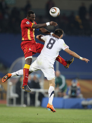 RUSTENBURG, SOUTH AFRICA - JUNE 26:  John Mensah of Ghana and Clint Dempsey of the United States jump for the ball during the 2010 FIFA World Cup South Africa Round of Sixteen match between USA and Ghana at Royal Bafokeng Stadium on June 26, 2010 in Ruste