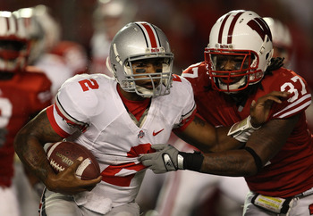 MADISON, WI - OCTOBER 16: Terrelle Pryor #2 of the Ohio State Buckeyes tries to break away from Kevin Claxton #37 of the Wisconsin Badgers at Camp Randall Stadium on October 16, 2010 in Madison, Wisconsin. Wisconsin defeated Ohio State 31-18.  (Photo by J