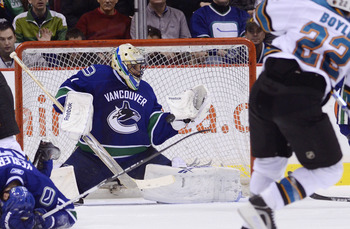 VANCOUVER, CANADA - JANUARY 20: Goalie Roberto Luongo #1 of the Vancouver Canucks makes a glove save on Dan Boyle #22 of the San Jose Sharks during the second period in NHL action on January 20, 2011 at Rogers Arena in Vancouver, BC, Canada.  (Photo by Ri