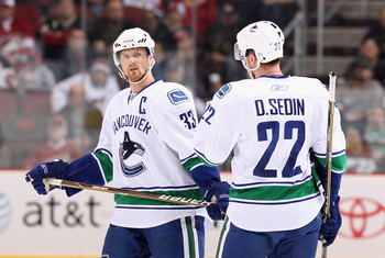 GLENDALE, AZ - MARCH 08:  Henrik Sedin #33 and Daniel Sedin #22 of the Vancouver Canucks talk during the NHL game against the Phoenix Coyotes at Jobing.com Arena on March 8, 2011 in Glendale, Arizona. The Canucks defeated the Coyotes 4-3 in overtime. (Pho
