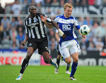 NEWCASTLE UPON TYNE, ENGLAND - MAY 07:  Birmingham player Sebastian Larsson (r) battles with Shola Ameobi during the Barclays Premier League game between Newcastle United and Birmingham City at St James' Park on May 7, 2011 in Newcastle upon Tyne, England