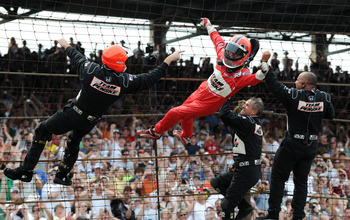 INDIANAPOLIS - MAY 24:  Helio Castroneves driver of the #3 Team Penske Dallara Honda climbs the front stretch fence with his teamates after winning the IRL IndyCar Series 93rd running of the Indianapolis 500 at the Indianapolis Motor Speedway on May 24, 2