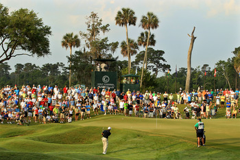 PONTE VEDRA BEACH, FL - MAY 12:  Tiger Woods chips to the second hole green as caddie Steve Williams looks on during the first round of THE PLAYERS Championship held at THE PLAYERS Stadium course at TPC Sawgrass on May 12, 2011 in Ponte Vedra Beach, Flori