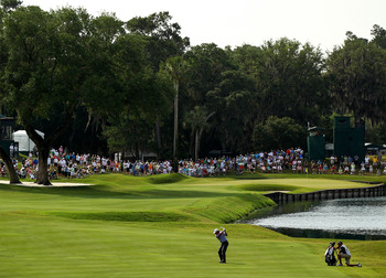 PONTE VEDRA BEACH, FL - MAY 13:  Phil Mickelson hits a shot on the 16th hole as his caddie Jim Mackay looks on during the second round of THE PLAYERS Championship held at THE PLAYERS Stadium course at TPC Sawgrass on May 13, 2011 in Ponte Vedra Beach, Flo