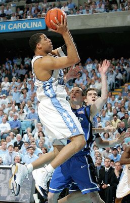 CHAPEL HILL, NC - MARCH 6:  J.J. Redick #4 of the Duke Blue Devils watches as Sean May #42 of the North Carolina Tar Heels goes to the basket on March 6, 2005 at the Dean E. Smith Center in Chapel Hill, North Carolina.  (Photo by Streeter Lecka/Getty Imag