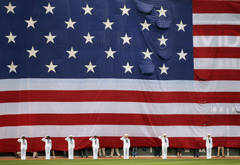 BOSTON, MA - MAY 02:  A giant flag covers the Green Monster as the national anthem is played before the game between the Boston Red Sox and the Los Angeles Angels on May 2, 2011 at Fenway Park in Boston, Massachusetts.  Both teams lined up on the baseline