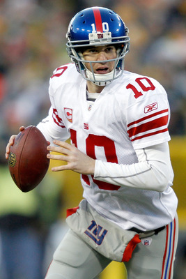 GREEN BAY, WI - DECEMBER 26: Eli Manning of the New York Giants rolls out of the pocket while playing the Green Bay Packers at Lambeau Field on December 26, 2010 in Green Bay, Wisconsin.  (Photo by Matthew Stockman/Getty Images)