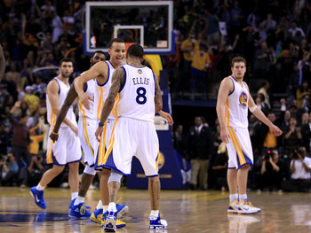 OAKLAND, CA - JANUARY 21:  Monta Ellis #8 is congratulated by Stephen Curry #30 of the Golden State Warriors after Ellis made a shot with less than a second left in regulation to send their game against the Sacramento Kings into overtime at Oracle Arena o