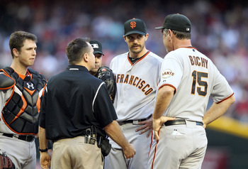 PHOENIX, AZ - APRIL 16:  Starting pitcher Barry Zito #75 of the San Francisco Giants talks with manager Bruce Bochy and a team trainer after an injury during the Major League Baseball game against the Arizona Diamondbacks at Chase Field on April 16, 2011