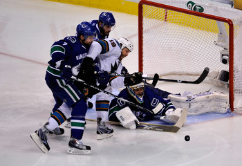 VANCOUVER, CANADA - MAY 15:  Ryan Kesler #17 and Dan Hamhuis #2 of the Vancouver Canucks defend Joe Thornton #19 of the San Jose Sharks goaltender Roberto Luongo #1 makes a save in the third period in the second period in Game One of the Western Conferenc