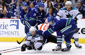 VANCOUVER, CANADA - MAY 15:  Torrey Mitchell #17 of the San Jose Sharks dives to poke at the puck as Ryan Kesler #17 and Christian Ehrhoff #5 of the Vancouver Canucks defend the play in Game One of the Western Conference Finals during the 2011 Stanley Cup