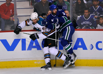 VANCOUVER, CANADA - MAY 15:  Jannik Hansen #36 of the Vancouver Canucks checks Kent Huskins #40 of the San Jose Sharks in Game One of the Western Conference Finals during the 2011 Stanley Cup Playoffs at Rogers Arena on May 15, 2011 in Vancouver, British