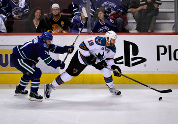 VANCOUVER, CANADA - MAY 15:   Joe Thornton #19 of the San Jose Sharks looks to make a pass play under pressure from Mason Raymond #21 of the Vancouver Canucks in Game One of the Western Conference Finals during the 2011 Stanley Cup Playoffs at Rogers Aren
