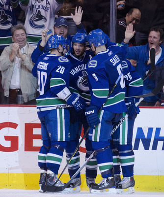 VANCOUVER, CANADA - APRIL 7: Ryan Kesler #17 of the Vancouver Canucks is congratulated by teammates Chris Higgins #20, Sami Salo #6 and Mikael Samuelsson #26 after scoring his third goal of the game against the Minnesota Wild during the third period in NH