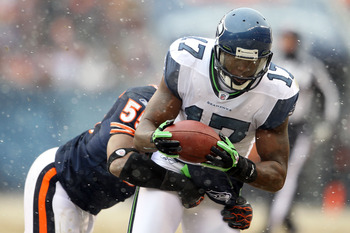 CHICAGO, IL - JANUARY 16:  Wide receiver Mike Williams #17 of the Seattle Seahawks makes a catch as he is tackled by Lance Briggs #55 of the Chicago Bears in the second quarter of the 2011 NFC divisional playoff game at Soldier Field on January 16, 2011 i
