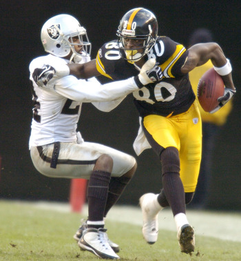 PITTSBURGH - DECEMBER 7:  Plaxico Burress #80 of the Pittsburgh Steelers is tackled by Charles Woodson #24 of the Oakland Raiders duirng the third quarter on December 7, 2003 at Heinz Field in Pittsburgh, Pennsylvania. The Steelers defeated the Raiders 27