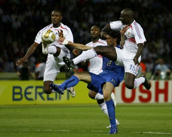 BERLIN - JULY 9: Eric Abidal (L) and Lilian Thuram (R) of France battle with Vincenzo Iaquinta (2nd R) of Italy for the ball during the FIFA World Cup Germany 2006 Final match between Italy and France at the Olympic Stadium on July 9, 2006 in Berlin, Germ