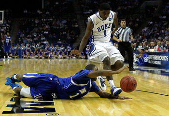 CHARLOTTE, NC - MARCH 18:  Mike Tuitt #11 of the Hampton Pirates drives for the ball in front of Kyrie Irving #1 of the Duke Blue Devils in the second half during the second round of the 2011 NCAA men's basketball tournament at Time Warner Cable Arena on