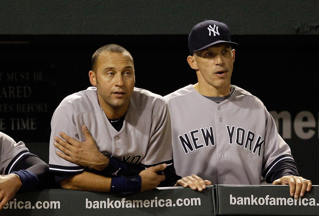 BALTIMORE, MD - APRIL 23:  Alex Rodriguez #13 of the New York Yankees (L) Derek Jeter #2 (C) and manager Joe Girardi #28 (R) look out from the dugout during the eighth inning of their 15-3 win over the Baltimore Orioles at Oriole Park at Camden Yards on A