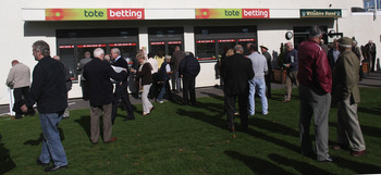 SALISBURY, ENGLAND - OCTOBER 12: Racegoers gather outside a Tote betting window before the first race to be run at Salisbury Racecourse on October 12, 2009 in Salisbury, England. Prime Minister Gordon Brown is expected to announce the sale of GBP £16 bill