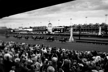 LOUISVILLE, KY - MAY 07:  (EDITORS NOTE: A VARIABLE FOCAL PLANE LENSE WAS USED AND WAS CONVERTED TO BLACK AND WHITE)  Jockey John Velazquez, riding Animal Kingdom #16 crosses the finish line to win the 137th Kentucky Derby at Churchill Downs on May 7, 201