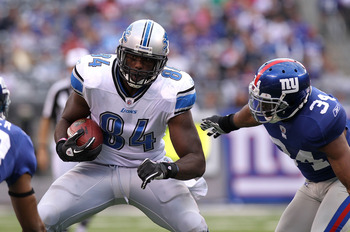EAST RUTHERFORD, NJ - OCTOBER 17: Brandon Pettigrew #84 of the Detroit Lions runs with the ball under pressure from Deon Grant #34 of the New York Giants at New Meadowlands Stadium on October 17, 2010 in East Rutherford, New Jersey.  (Photo by Nick Laham/