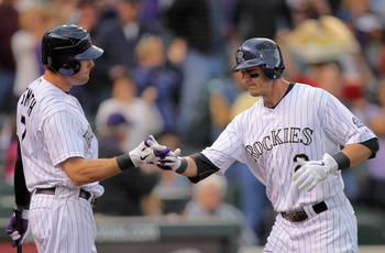 DENVER, CO - MAY 10:  Troy Tulowitzki #2 of the Colorado Rockies is welcomed home after his solo homerun off of starting pitcher Mike Pelfrey #34 of the New York Mets by Seth Smith #7 of the Colorado Rockies in the second inning at Coors Field on May 10,