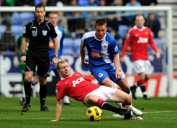 WIGAN, ENGLAND - FEBRUARY 26:  James McCarthy of Wigan Athletic competes with Paul Scholes of Manchester United during the Barclays Premier League match between Wigan Athletic and Manchester United at the DW Stadium on February 26, 2011 in Wigan, England.